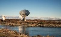 Den klassiska 25-metersantennen har stått vid Onsala rymdobservatorium sedan 1960-talet. I bakgrunden syns de nya tvillingteleskopen. Foto: David Magnusson.