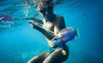 Dykaren Basong, 65 år, har harpunerat en fisk. I bältet bär han en gul mätare som registrerar tid och djup. Bild: Erik Abrahamsson.